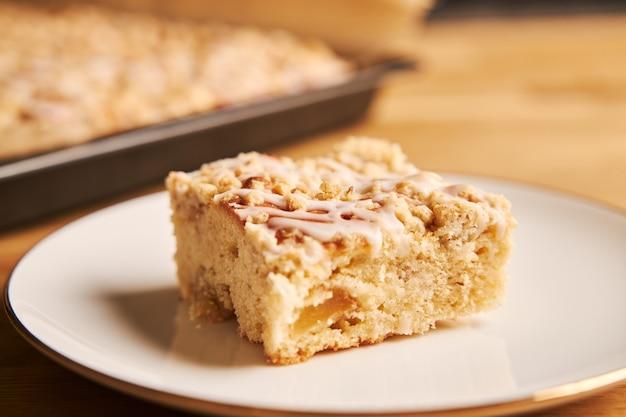 Colpo del primo piano di una fetta di una deliziosa torta di mele su un piatto su un tavolo di legno