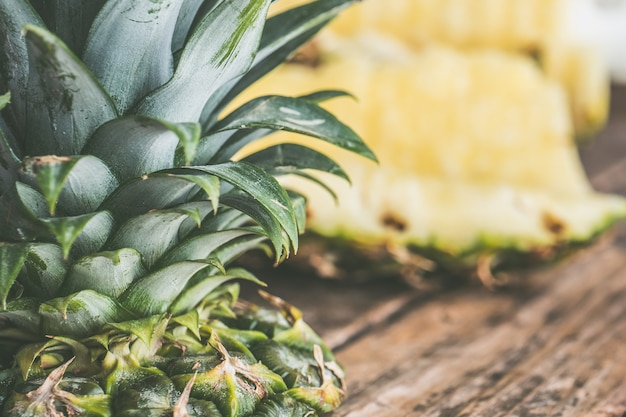 Closeup shot of sliced pineapple and pointy leaves on a wooden background