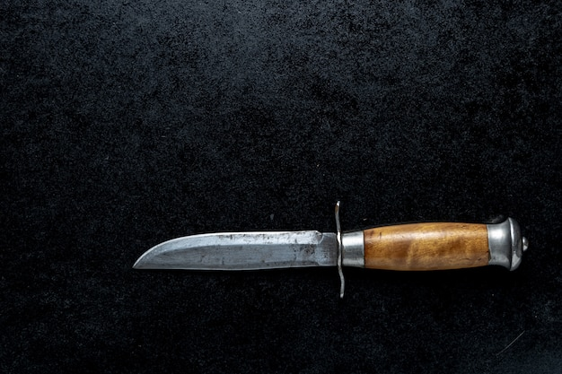 Closeup shot of a small sharp knife with a brown handle  on a black background