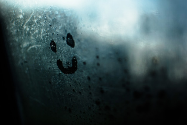 Closeup shot of a smiley face drawn on the steamed glass