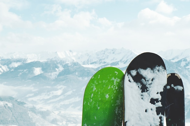 Closeup shot of snowboards covered in snow in the mountains