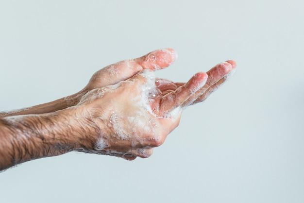Colpo del primo piano delle mani insaponate di una persona