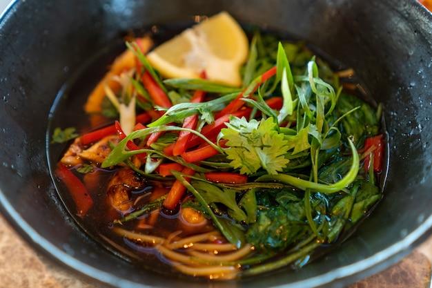 Closeup colpo di zuppa con verdure, limone e verdure in un piatto nero