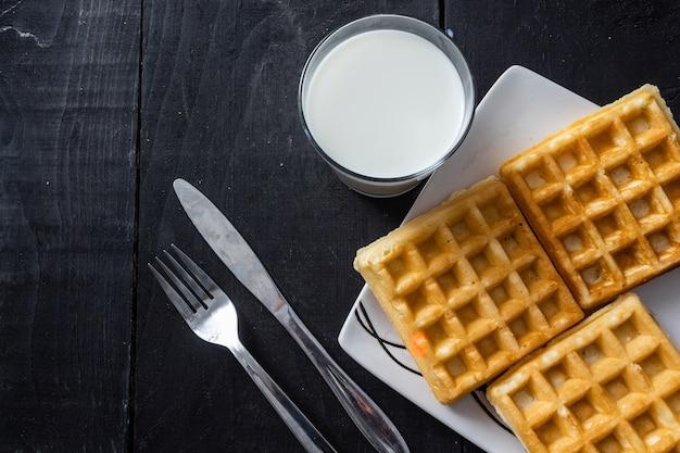 Colpo del primo piano di cialde quadrate e bicchiere di latte su un tavolo di legno