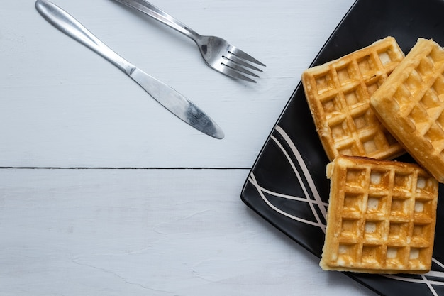 Closeup shot of square waffles on a wooden table background