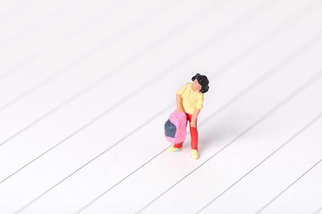 Primo piano di una statuina di una studentessa che porta il suo zaino