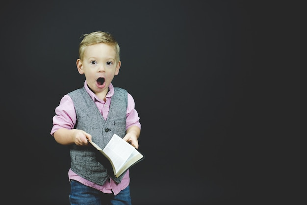 Closeup shot of a surprised child holding the bible