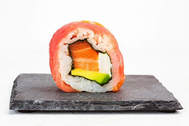 Closeup shot of a sushi roll on a black stone plate