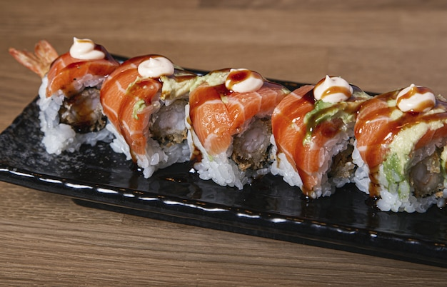 Closeup shot of sushi stuffed with prawn covered with salmon and avocado.