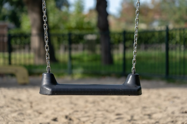 Closeup shot of a swing in front of a metal fence and trees
