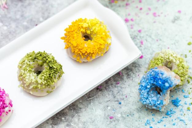 Colpo del primo piano del ripiano del tavolo di ciambelle colorate crude vegane