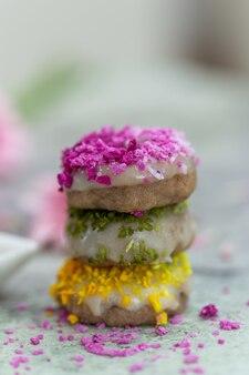 Colpo del primo piano del tavolo di ciambelle colorate crude vegane raw