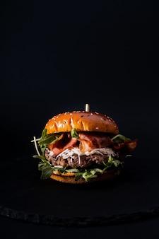 Primo piano di un gustoso hamburger isolato su una superficie nera