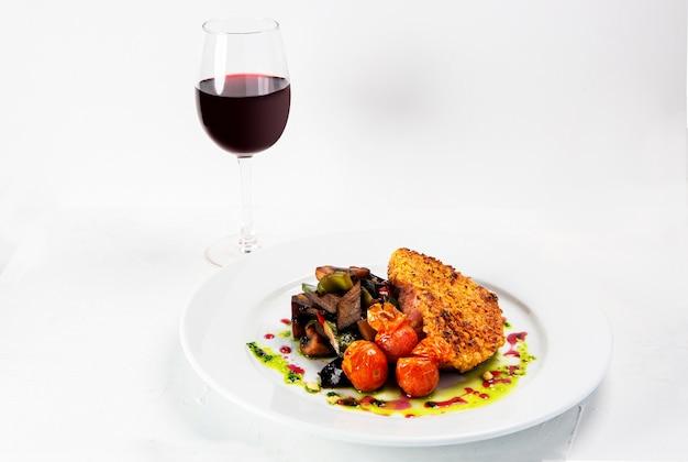 Colpo del primo piano di un piatto dall'aspetto gustoso vicino a un bicchiere di vino isolato su priorità bassa bianca