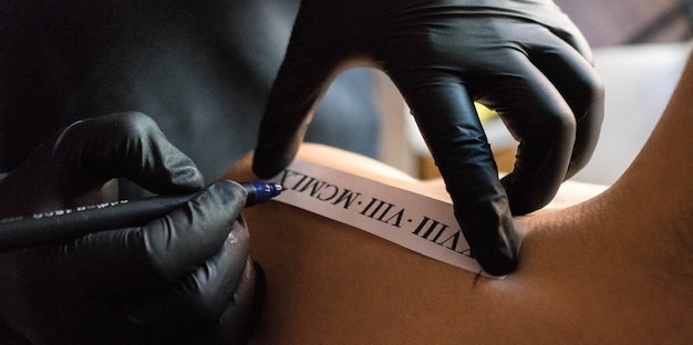 Closeup shot of a tattoo artist placing a design on a client's shoulder