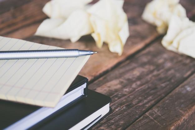 Colpo del primo piano dei libri di testo con una penna grigia e pezzi di carta sgualciti intorno su una superficie di legno