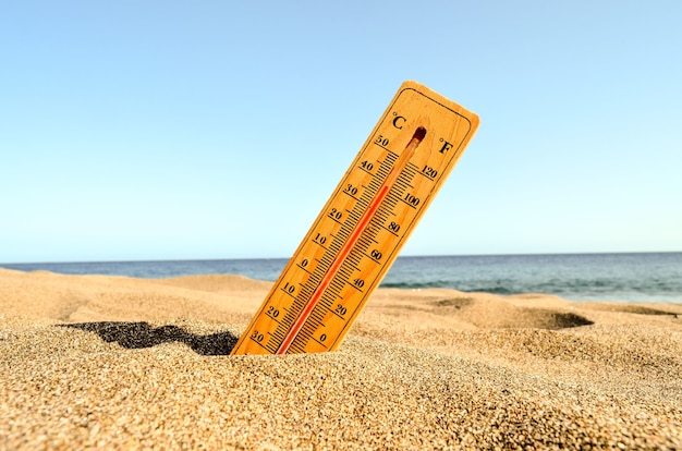 A closeup shot of a thermometer in the beach sand