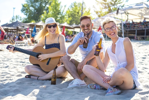 Closeup shot of three caucasian friends having fun on the beach with a guitar