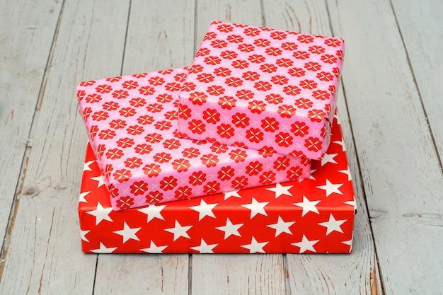 Colpo del primo piano di tre scatole regalo impilate una sopra l'altra su una superficie di legno
