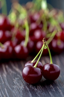 Closeup shot of three maroon cherries set up vertically on a wooden surface