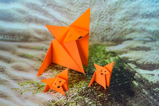 Closeup shot of three orange paper origamis with faces drawn on them on a patterned surface