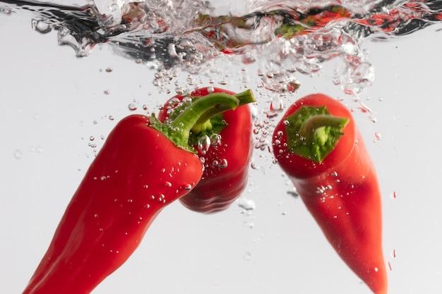 Colpo del primo piano di tre peperoni rossi di tabasco nell'acqua