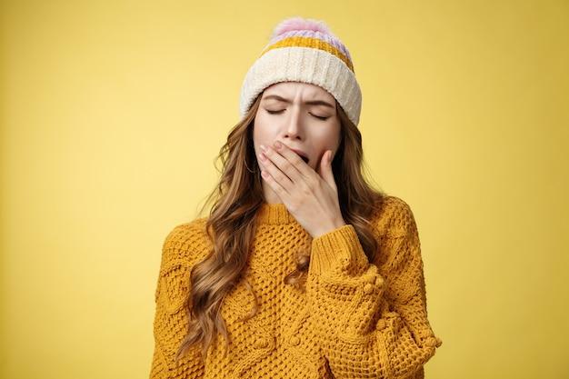 クローズアップショット疲れたあくびかわいい疲れ果てたヨーロッパの女性が帽子のセーターカバーを身に着けている口を開けた感じ...