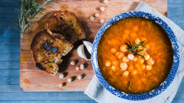 Colpo del primo piano della zuppa di ceci italiana tradizionale con rosmarino e pane