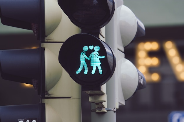 Closeup shot of a traffic light showing a man and a woman holding hands