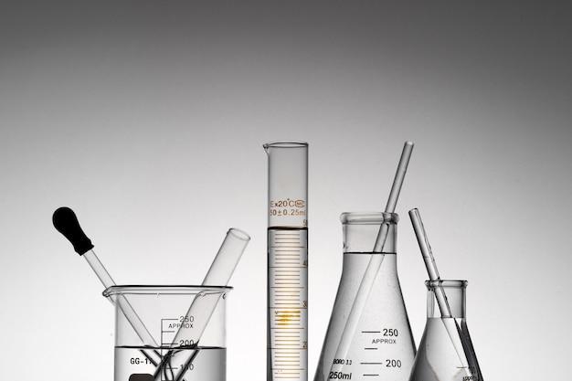 Colpo del primo piano di boccette da laboratorio trasparenti, bicchieri e tubi