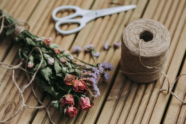 Colpo del primo piano di spago con le forbici bianche e fiori secchi su una superficie di legno