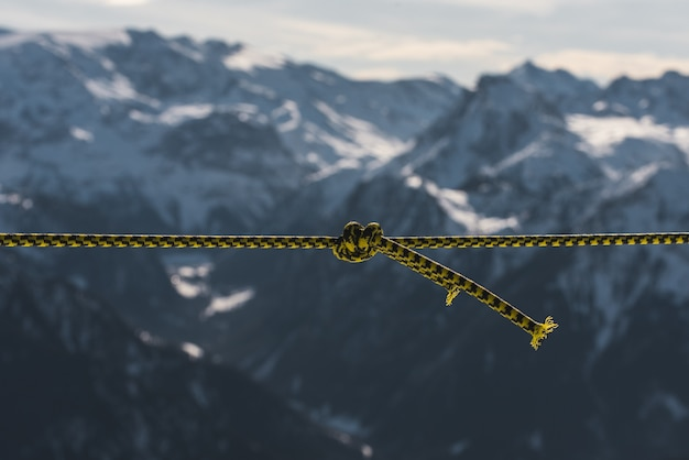 Closeup shot of a twisted rope in front of the mountains covered in snow
