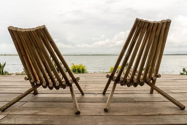Colpo del primo piano di due sedie davanti all'oceano sotto un cielo nuvoloso