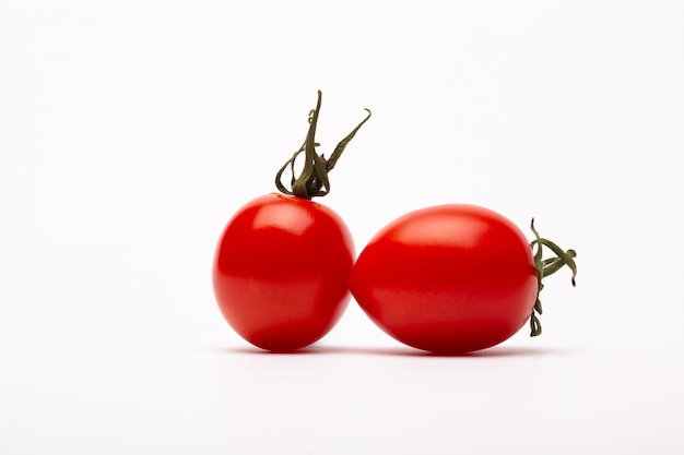 Closeup shot of two cherry tomatoes on a white background - perfect for a food blog