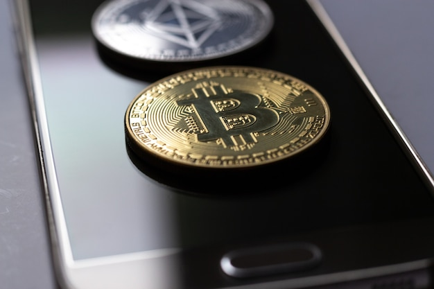 Closeup shot of two coins placed on top of a mobile phone