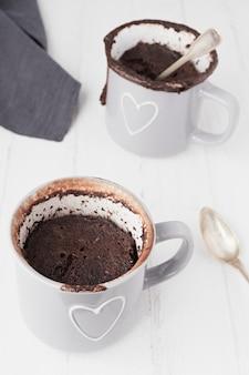 Colpo del primo piano di due tazze di caffè isolate su una superficie bianca