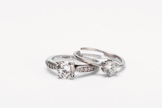 Closeup shot of two diamond rings on a white surface