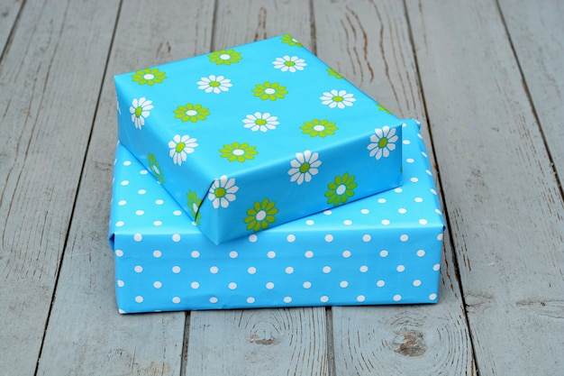Closeup shot of two gift boxes in blue wrapping stacked on top of each other on a wooden surface
