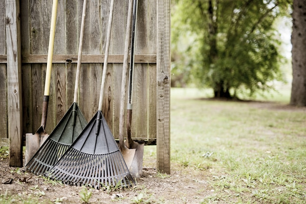 Closeup shot of two leaf rakes and shovels leaned against a wooden fence with a blurred background