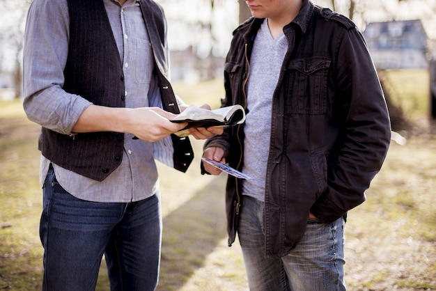 Closeup shot of two males standing near each other and reading the bible