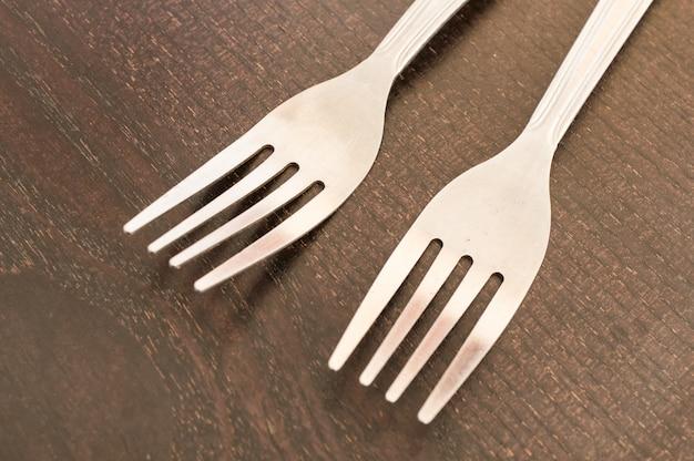 Colpo del primo piano di due forchette di plastica bianche su una superficie di legno