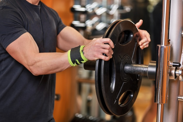 Closeup shot of unidentifiable muscular male picking up heavy dumbbell weights from equipment rack in modern gym.
