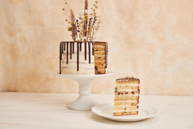 Closeup shot of a vanilla cake with chocolate drip and flowers on top