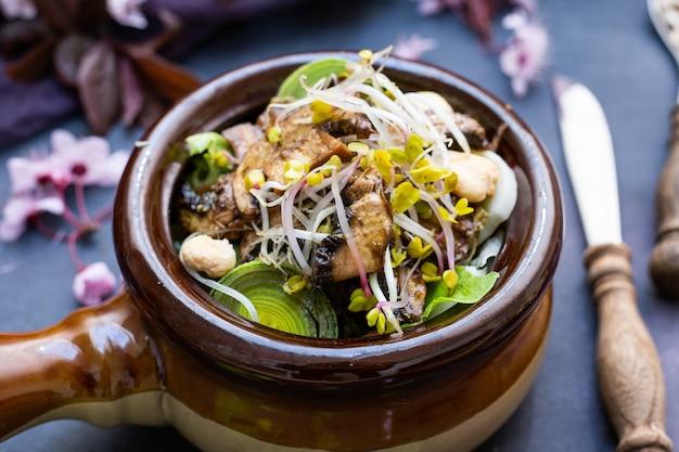 Primo piano di un pasto vegano con funghi, cipolle, carote e porri