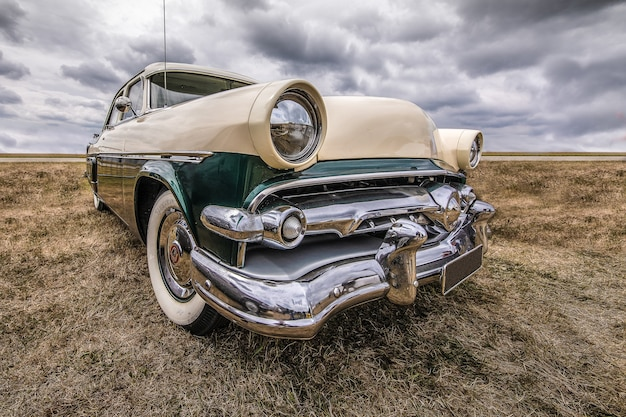 Closeup shot of a vehicle on a dry field under a cloudy sky