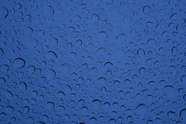 Colpo del primo piano di gocce d'acqua grandi e piccole sul vetro blu - perfetto per lo sfondo