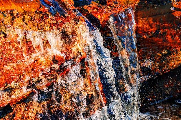 Colpo del primo piano dell'acqua che versa attraverso le rocce