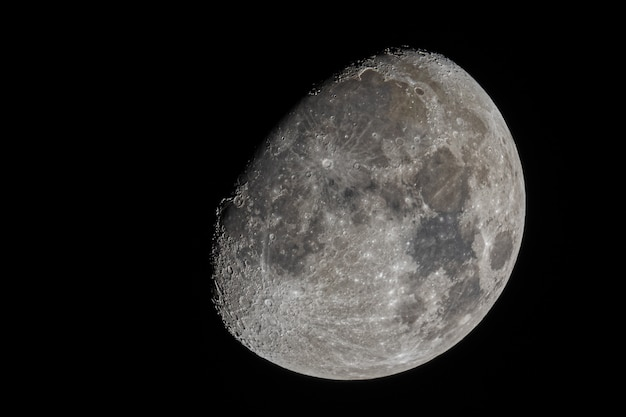 Closeup shot of the waxing gibbous moon with visible craters and the sea of tranquility