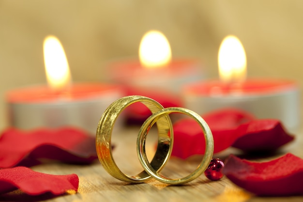 Closeup shot of wedding rings with a background of beautiful red roses and candles on the table