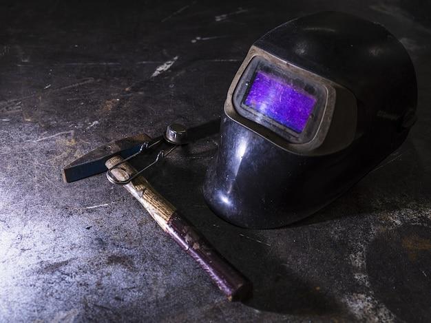 Colpo del primo piano di un casco per saldatura vicino a un hummer